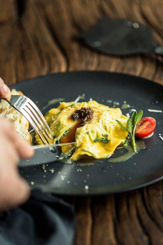 Foto de prato do cardápio, Ravioloni de gema de ovo caipira na manteiga e sálvia, perfumado ao molho de trufa negra